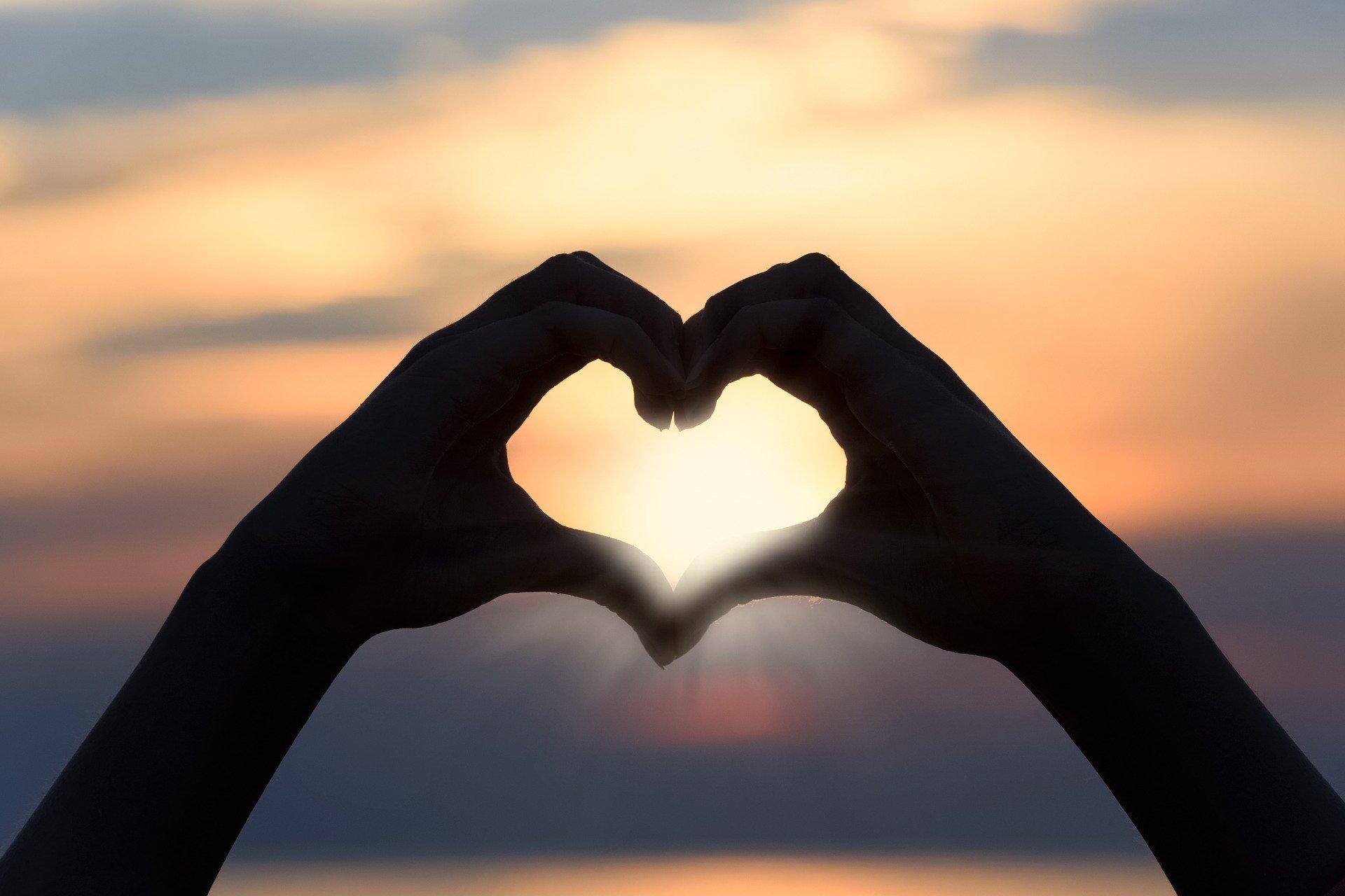 kuvassa käsistä muodotettu sydän ja auringonlasku