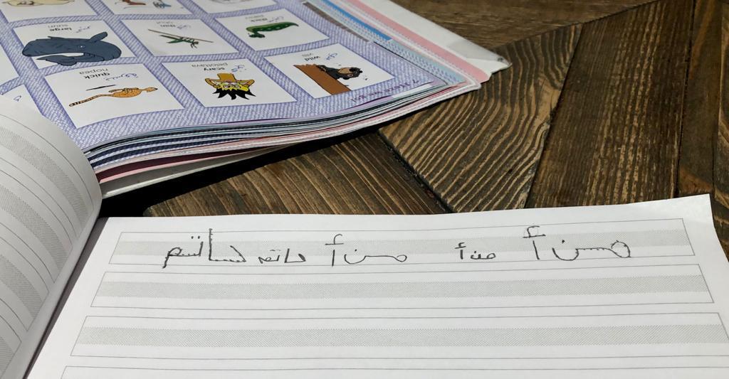 Kuvassa on oppikirja ja vihko, jossa arabiankielistä kirjoitusta.