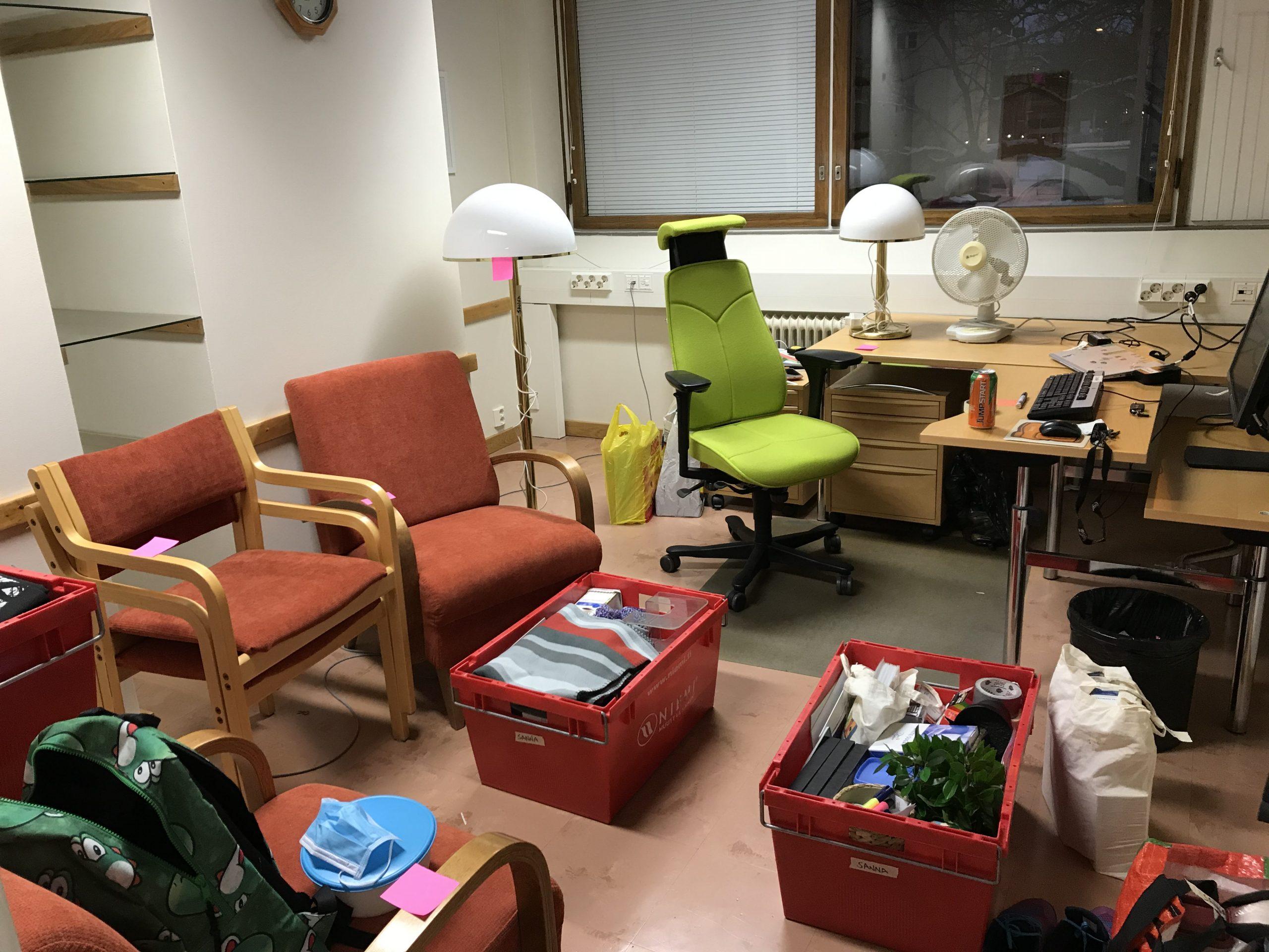 kuvassa työhuone, jossa tavarat ovar muuttolaatikoissa